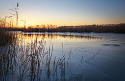 Winter landscape with sunset sky and frozen river. Royalty Free Stock Images