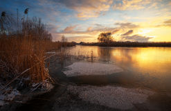 Winter landscape with sunset sky and frozen river. Stock Photo