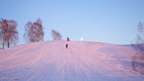 Winter landscape. sunset time. people climb the snowy hill stock video