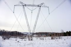 Support overhead power lines on a wooded area in winter. Winter landscape. Support overhead power lines on a wooded area in winter stock photo