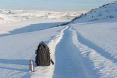 Winter landscape,thermos, and backpack are on the snow . Royalty Free Stock Photo