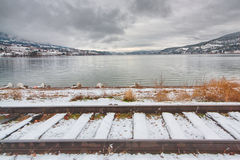 Winter Landscape of Train Tracks in Front of Lake. Landscape of snow covered train tracks in front of Wood lake Stock Photo