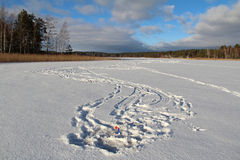 Winter landscape with traps for the fish on a frozen lake in the forest. Stock Photo