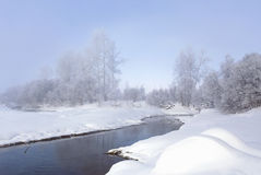 Winter landscape. Trees and bushes with hoarfrost. The water in the river floating mist. cold season. a grayish-white crystalline Royalty Free Stock Images