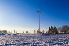 Winter landscape trees snow covered fields windmills Stock Images