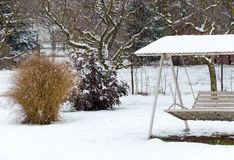 Winter landscape - trees, swing and falling snow Royalty Free Stock Images
