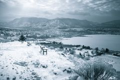 Winter landscape view of city, lake, and snow-capped mountains royalty free stock photography