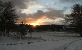 A winter landscape view at Kinloch Rannoch,  Perthshire, Scotland, as the sunrises over the tree lined Mountains..... A stunning winter landscape view at Stock Image