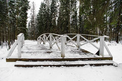 Winter landscape with white wooden bridge. In a snowy pine forest Royalty Free Stock Images