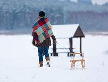 Winter landscape with woman pulling sled Royalty Free Stock Images
