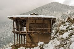 Winter landscape. Wooden house in the snow. Snow caped mountain range in blurred background. India royalty free stock photography