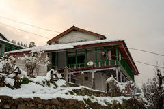 Winter landscape. Wooden house in the snow. Snow caped mountain range in blurred background. India stock images