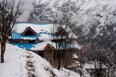 Winter landscape. Wooden house in the snow. Snow caped mountain range in blurred background. India stock photos