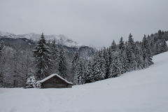 Winter landscape with wooden house, trees and mountains on background near Garmisch-Partenkirchen. Germany. Stock Photos