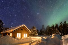 Winter landscape with wooden house under a beautiful starry sky. And Northern Lights, Sweden royalty free stock images