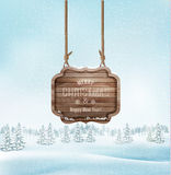 Winter landscape with a wooden ornate Merry christmas sign. Royalty Free Stock Photography