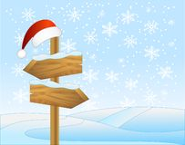 Winter landscape with a wooden  pointer and christmas cap Stock Photos