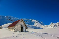 Winter landscape with wooden toolshed at Balea lake, Sibiu county, Romania. Winter landscape with wooden toolshed and Fagaras Mountains covered in thick layer royalty free stock photography
