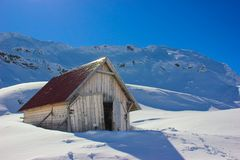 Winter landscape with wooden toolshed at Balea lake, Sibiu county, Romania. Winter landscape with wooden toolshed and Fagaras Mountains covered in thick layer Stock Photos