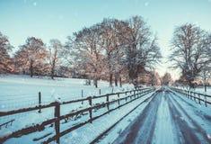 Winter-Landschaft des Zauns Lined Snowy Track stockfotografie