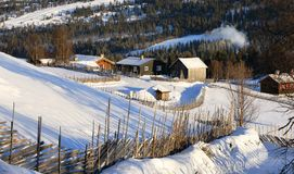 Winter landscape with wooden houses and traditional norwegian wooden fence. In warm sunlight royalty free stock photo