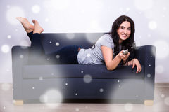 Winter leisure concept - woman lying on sofa and watching tv at Royalty Free Stock Image