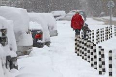 Winter Leute gehen auf einen sehr schneebedeckten Bürgersteig und eine Straße Leute treten auf eine eisige Bahn, eisiger Bürgerst Lizenzfreie Stockfotografie