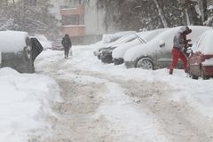 Winter Leute gehen auf einen sehr schneebedeckten Bürgersteig und eine Straße Leute treten auf eine eisige Bahn, eisiger Bürgerst Lizenzfreies Stockbild