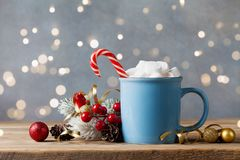 Winter lifestyle with cup of hot cocoa with marshmallows and Christmas decoration on wooden background. Bokeh effect. Winter lifestyle with cup of hot cocoa with royalty free stock images