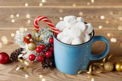 Winter lifestyle with cup of hot cocoa with marshmallows and Christmas decoration on wooden background. Bokeh effect. royalty free stock photos