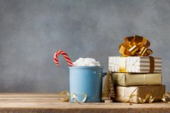 Winter lifestyle with cup of hot cocoa with marshmallows and Christmas gift or present boxes and holiday decorations. On wooden background royalty free stock photos