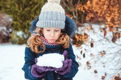 Winter lifestyle portrait of happy kid girl playing snowballs on the walk. On backyard stock image