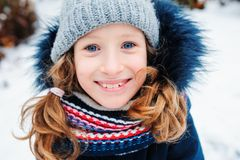 Winter lifestyle portrait of happy kid girl playing snowballs on the walk