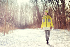 Winter lifestyle woman walking outdoors in forest. Winter happy woman walking in snow outdoors nature. Joyful young person relaxing on an outdoor walk activity Royalty Free Stock Image