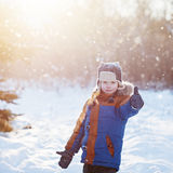 Winter little child playing throws up snow outdoors during snowfall. Active outoors leisure with children in winter on cold snowy Royalty Free Stock Images