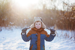 Winter little child playing throws up snow outdoors during snowfall. Active outoors leisure with children in winter on cold snowy Stock Images