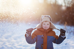 Winter little child playing throws up snow outdoors during snowfall. Active outoors leisure with children in winter on cold snowy. Days stock photo