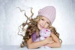 Winter little girl hug teddy bear smiling