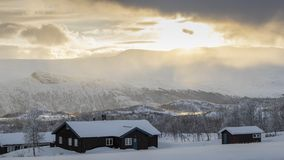 Winter log cabins in snow landscape in Norway. Winter log cabins in the snow in Norway surrounded by a frosty landscape royalty free stock photos