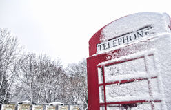 Winter in London. Classic red London phone booth in the winter, covered in snow Stock Images