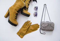 Winter look. Suedeyellow  boots, blue sunglasses, snakeskin clutch and leather yellow gloves Royalty Free Stock Images