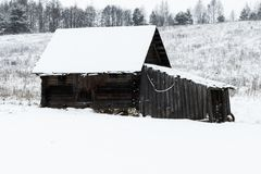 Winter, a lot of snow. Old wooden barn. standing in the wasteland royalty free stock photography