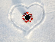 Winter Love. Cup of Coffee and Valentine's Heart on snow Royalty Free Stock Image