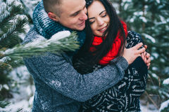 Winter Love Story. Beautiful young couple in winter forest Stock Image