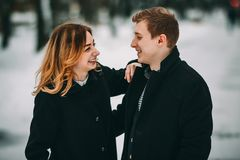 Winter LoveStory in Valentine`s day. Girl and guy happy and smiling Stock Photos