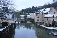 Winter in Luxemburg City. Buildings in Grund, district of Luxemburg City,  under snow. Mosel river in the center of the city Stock Photo