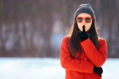 Winter-Mädchen mit dem Finger auf ihren Lippen, die ein Geheimnis halten lizenzfreie stockfotografie