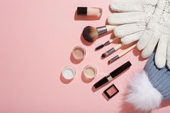Winter makeup products. Variety of cosmetics products next to mittens and bobble hat on pink background, top view Royalty Free Stock Photo