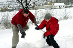 Winter - Making Snowman. Man and boy making snowman Stock Photo