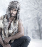 Winter male fashion. Fashion portrait of male model wearing fur in winter wonderland Royalty Free Stock Image